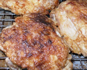 Fried Chicken resting on a cooling rack.
